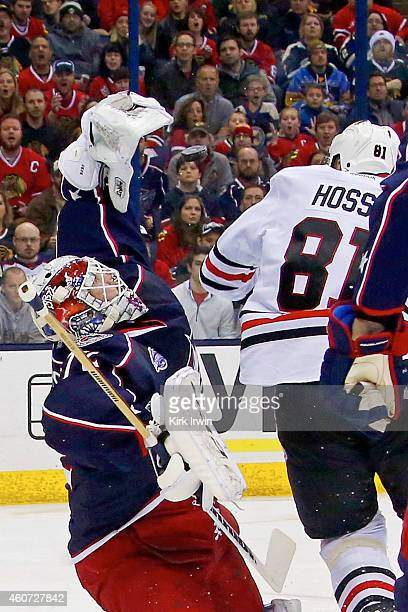 Marian Hossa of the Chicago Blackhawks knocks the puck out of the glove of Sergei Bobrovsky of the Columbus Blue Jackets during the first period on...