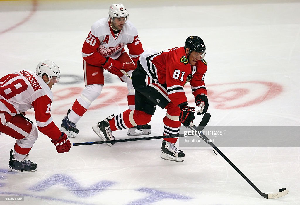Marian Hossa #81 of the Chicago Blackhawks moves between Joakim Andersson #18 (L) and Drew Miller #20 of the Detroit Red Wings during a preseason game at the United Center on September 22, 2015 in Chicago, Illinois. The Blackhawks defeated the Red Wings 5-4 in overtime.