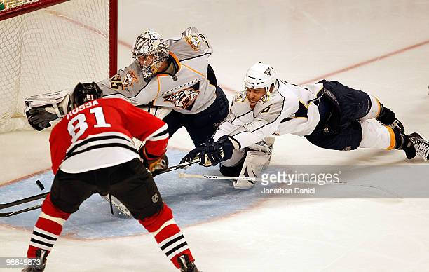 Marian Hossa of the Chicago Blackhawks scores the gamewinning goal in overtime as Pekka Rinne and Shea Weber of the Nashville Predators dive to try...