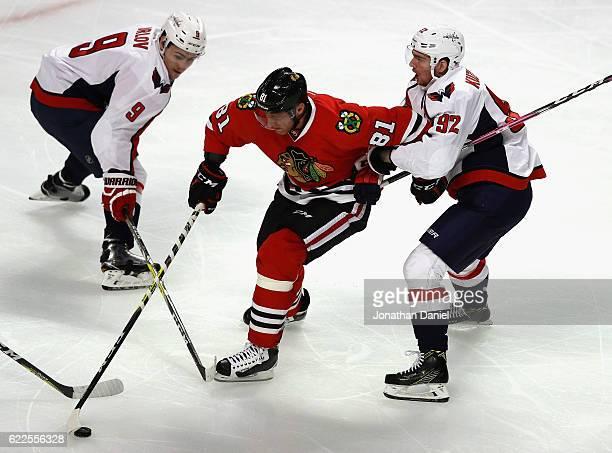 Marian Hossa of the Chicago Blackhawks skates between Dmitry Orlov and Evgeny Kuznetsov of the Washington Capitals at the United Center on November...