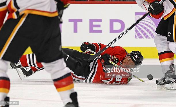 Marian Hossa of the Chicago Blackhawks tries to control the puck after falling to the ice against the Calgary Flames at the United Center on October...