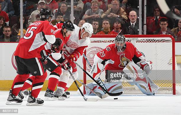 Marian Hossa the Detroit Red Wings drives to the net with the puck as Jason Spezza and Martin Gerber of the Ottawa Senators defend at Scotiabank...