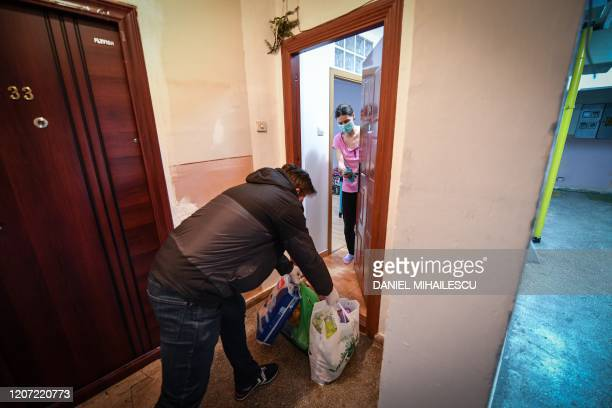 Marian Raduna a member of Geeks for Democracy NGO delivers her shopping to a young mother who stays confined at her home due to the novel coronavirus...