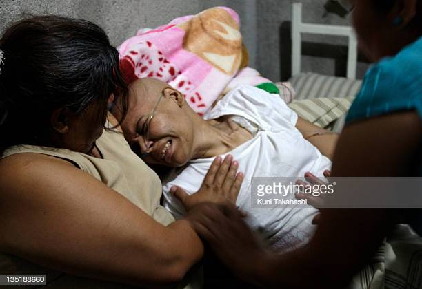 Mariana de la Torre 3rd from left suffers from pain as she is comforted by her mother Mary Elena left and church members at Mariana's family's house...