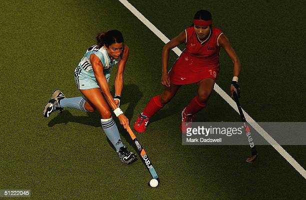 Mariana Gonzalez Oliva of Argentina plays the ball away from Qiuqi Chen of China in the women's field hockey bronze medal match on August 26 2004...