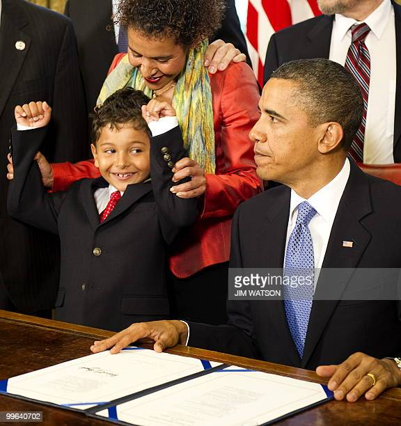 Mariane Pearl holds up Adam Daniel Pearl's arms after US President Barack Obama signed the Freedom of the Press Act in the Oval Office of the White...