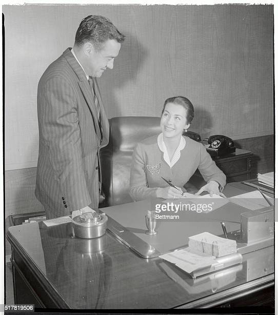 Marianne Cook smiles at Edward Muhl, Universal International Vice President, before signing her long term movie contract at the studio in Hollywood....