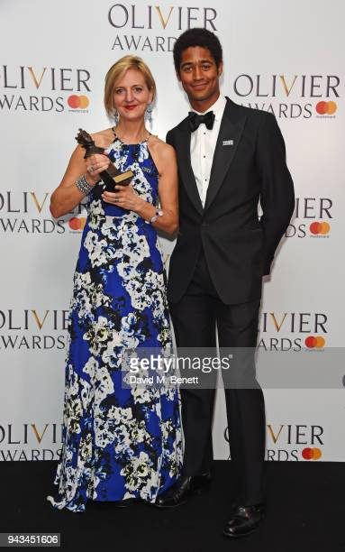 Marianne Elliott accepting the Best Revival award for 'Angels In America' and Alfred Enoch pose in the press room during The Olivier Awards with...