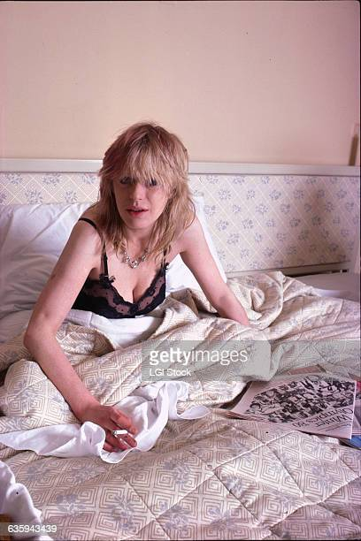 Marianne Faithfull is sitting in bed smoking a cigarette and reading a newspaper