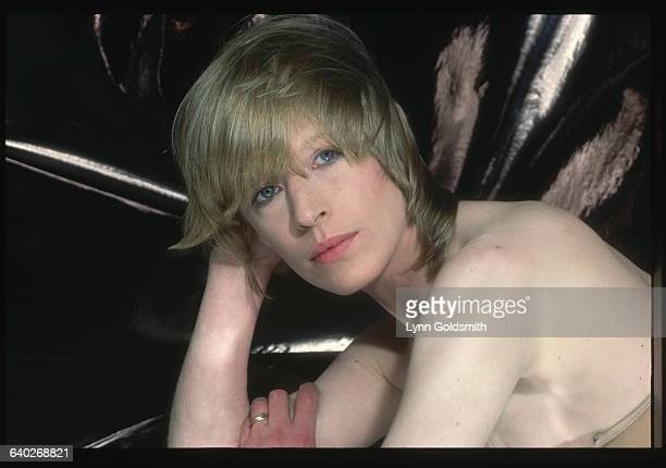 Marianne Faithfull poses without her shirt her breasts hidden as she leans forward resting her head on her hand Undated photograph