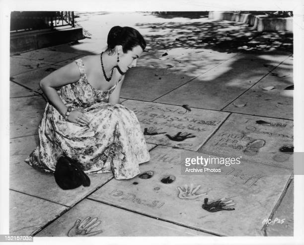 Marianne Koch pauses to read inscriptions in front of Grauman's Chinese theater in publicity portrait for the film 'Four Girls in Town', 1957.