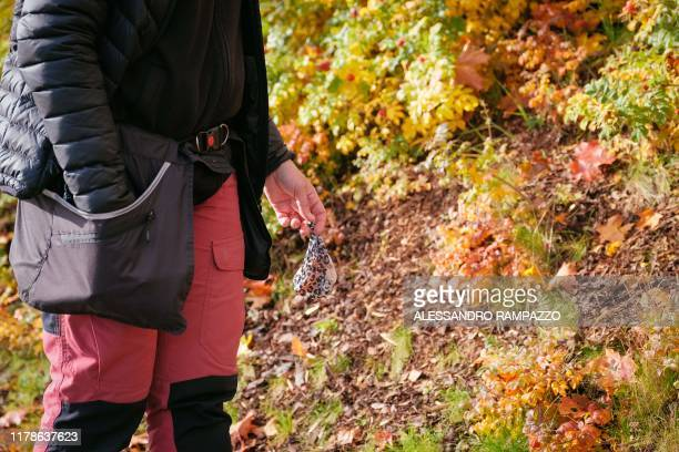 Marianne Mayer dog trainer and promoter of a campaign that aims to give dog poo a new life grabs some trash from the ground in Vantaa Finland on...