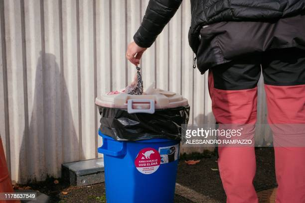 Marianne Mayer dog trainer throws some trash in a bin with a sticker reading Do you want to give poo a new life in Vantaa Finland on October 7 2019...