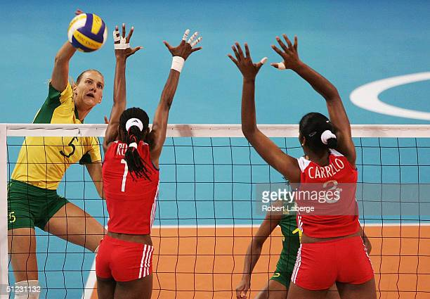 Marianne Stein of Brazil spikes the ball against Yumilka Ruiz Luaces and Nancy Carrillo de la Paz of Cuba in the women's indoor Volleyball bronze...