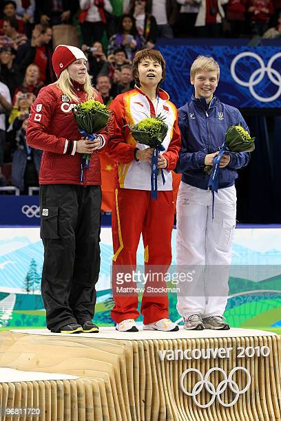 Marianne StGelais of Canada celebrates winning silver Wang Meng of China gold and Arianna Fontana of Italy bronze during the flower ceremony for the...