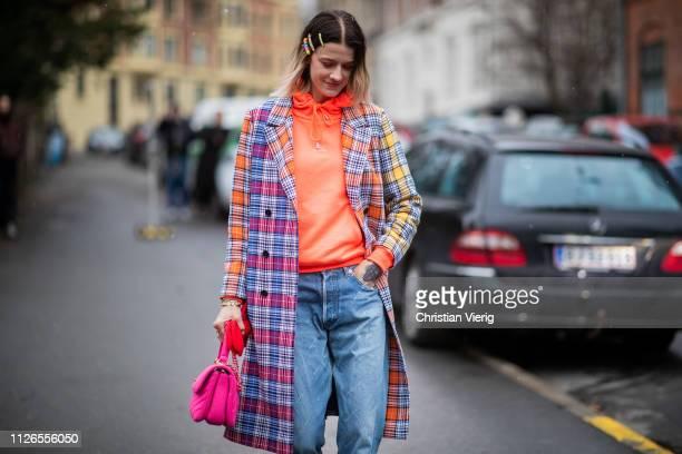 Marianne Theodorsen is seen wearing two tone plaid coat orange Holzweiler hoody denim jeans outside By Malene Birger during the Copenhagen Fashion...