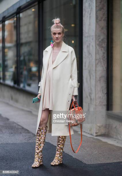 Marianne Theodorsen wearing a trench coat pastel dress boots and Balenciaga bag outside Bik Bok Runway Award on August 24 2017 in Oslo Norway