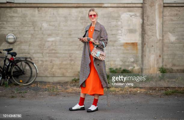Marianne Theodorsen wearing orange dress checked coat Fendi bag red socks seen outside Ganni during the Copenhagen Fashion Week Spring/Summer 2019 on...