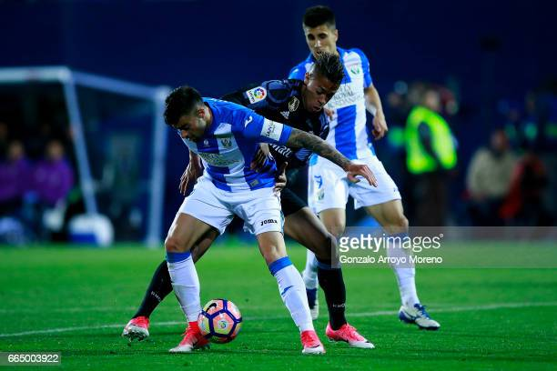 Mariano Diaz of Real Madrid CF competes for the ball with Diego Rico of Deportivo Leganes during the La Liga match between CD Leganes and Real Madrid...