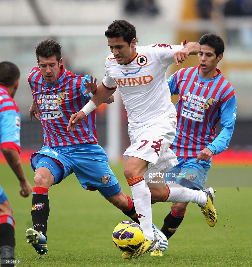 Mariano Izco (L) and Pablo Barrientos (R) of Catania competes for the ball with Marquinho of Roma during the Serie A match between Calcio Catania and AS Roma at Stadio Angelo Massimino on January 13, 2013 in Catania, Italy.