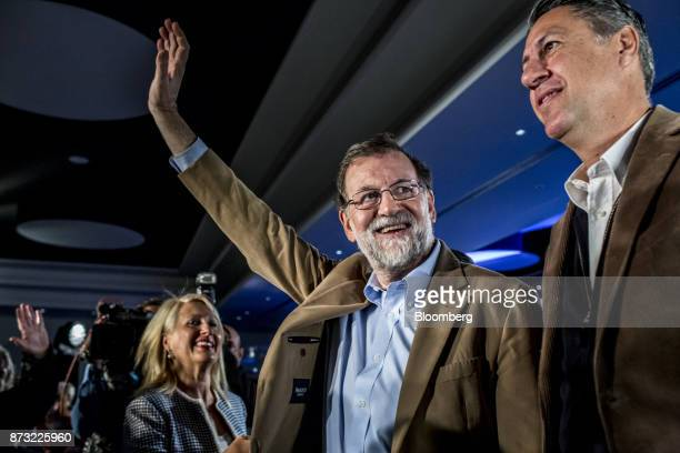 Mariano Rajoy Spain's prime minister and leader of the People's Party center waves to the audience as he stands next to Xavier García Albiol leader...