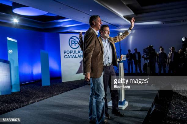 Mariano Rajoy Spain's prime minister and leader of the People's Party right waves to the audience as he stands next to Xavier García Albiol leader of...