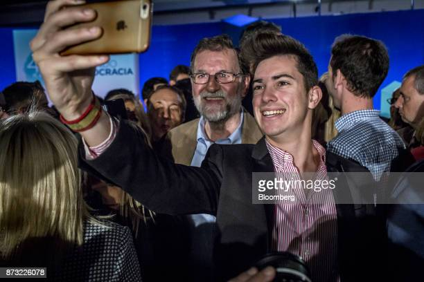 Mariano Rajoy Spain's prime minister and leader of the People's Party center poses for a photograph with an attendee during an election campaign...