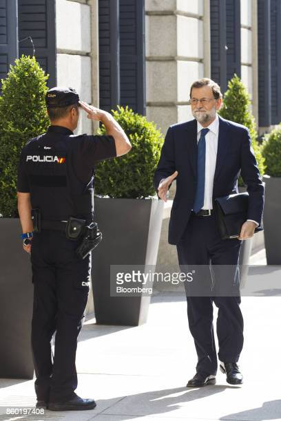 Mariano Rajoy Spain's prime minister right prepares to shake the hand of a saluting policeman as he arrives at the parliament in Madrid Spain on...
