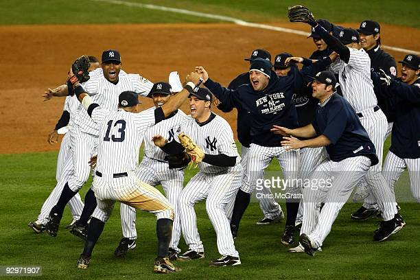 Mariano Rivera and Mark Teixeira of the New York Yankees run towards Alex Rodriguez and his teammates as they celebrate after their 73 win against...