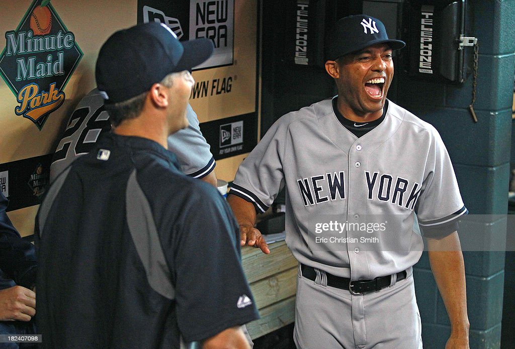 Mariano Rivera #42 (R) of the New York Yankees jokes with Andy Pettitte #46 in the dugout before a game against the Housotn Astros on September 29, 2013 at Minute Maid Park in Houston, TX.