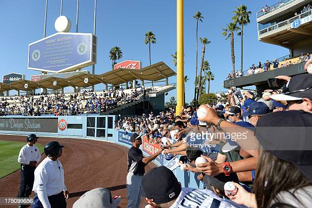 Mariano Rivera of the New York Yankees signs autographs in the outfield during batting practice before the game against the Los Angeles Dodgers at...