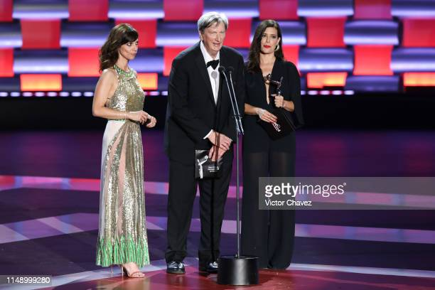 Maribel Verdu president of the Academy of Motion Picture Arts and Sciences John Bailey and Angie Cepeda on stage during the Premios Platino 2019 at...