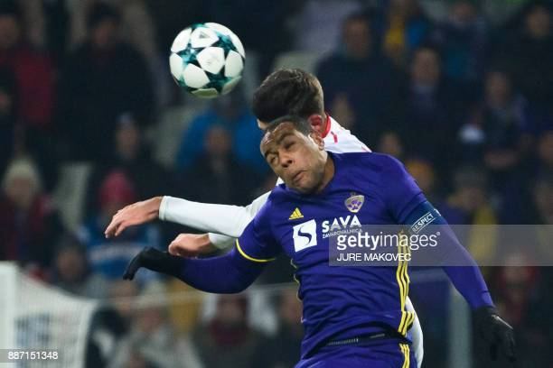 Maribor's Brazilian forward Marcos Tavares heads the ball with French defender Clement Lenglet during the UEFA Champions League Group E football...