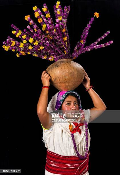 Maricela Juarez Vazquez poses for a photograph with her traditional costume during the presentation of the Huey Atlixcayotl Festival on September 29...