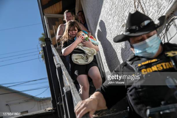 Maricopa County constable Darlene Martinez escorts a family out of their apartment after serving an eviction order for non-payment on September 30,...