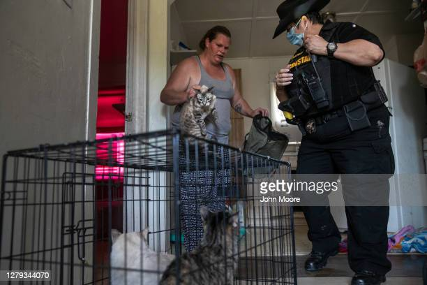 Maricopa County constable Darlene Martinez helps a single mother of two cage her pets after recieving an eviction order for non-payment of rent on...