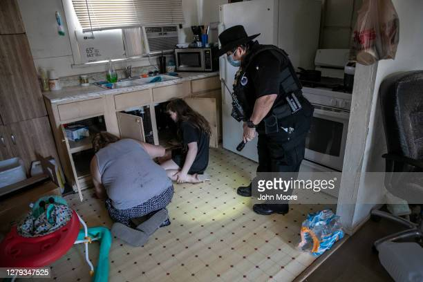 Maricopa County constable Darlene Martinez helps family members search for their cats after serving an eviction order for non-payment of rent on...