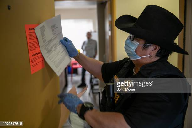 Maricopa County constable Darlene Martinez posts an eviction order for non-payment of rent on October 1, 2020 in Phoenix, Arizona. Thousands of...