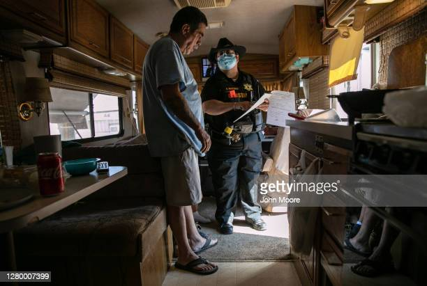 Maricopa County constable Darlene Martinez shows Hector Medrano court documents ordering his family's eviction from an RV park on October 07, 2020 in...