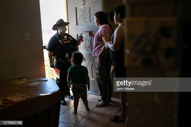 Maricopa County constable Darlene Martinez speaks to a renter by phone about an eviction order as the tenant's children translate on October 1, 2020...