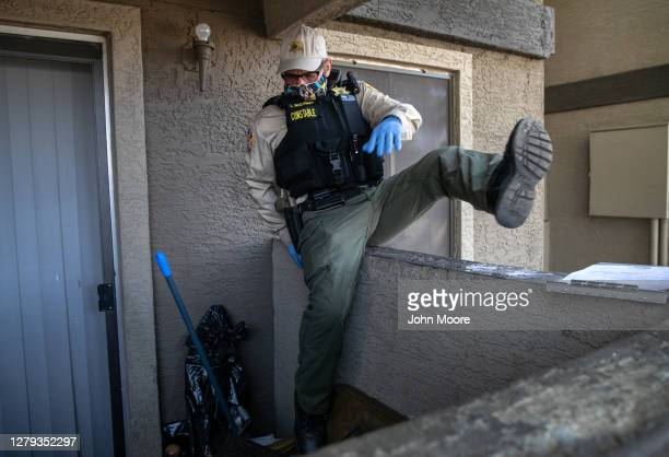 Maricopa County constable Lenny McCloskey climbs into the rear of an apartment to enter and post an eviction order on October 7, 2020 in Phoenix,...