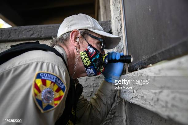 Maricopa County constable Lenny McCloskey peers into an apartment before serving an eviction order on October 7, 2020 in Phoenix, Arizona. Thousands...