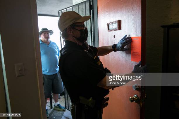 Maricopa County constable Lenny McCloskey posts an eviction order on the door of an apartment September 30, 2020 in Glendale, Arizona. Thousands of...