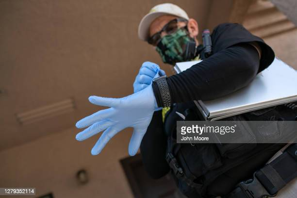 Maricopa County constable Lenny McCloskey puts on protective gloves before evicting an apartment resident for non-payment of rent on October 5, 2020...