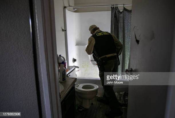 Maricopa County constable Lenny McCloskey searches an apartment while serving an eviction order on October 7, 2020 in Phoenix, Arizona. Thousands of...