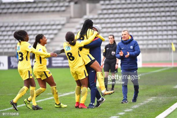 Marie Antoinette Katoto of PSG jumps into the arms of PSG assistant coach Bernard Mendy after putting their side 20 ahead as PSG coach Patrice Lair...