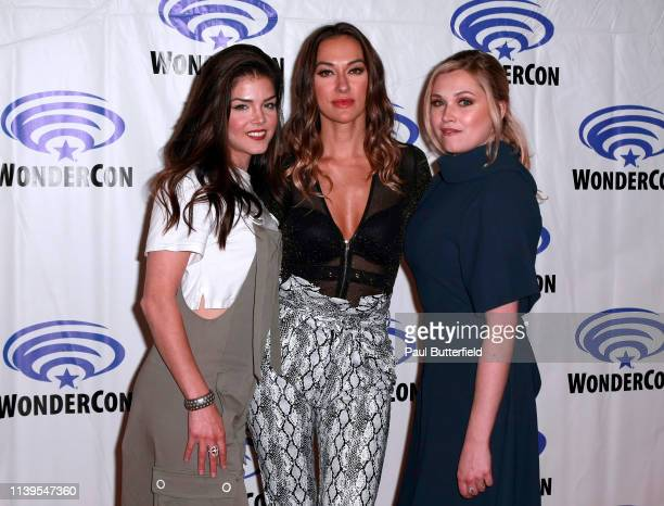 Marie Avgeropoulos Tasya Teles and Eliza Taylor attend the 'The 100' press line during WonderCon 2019 at Anaheim Convention Center on March 31 2019...