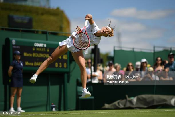 Marie Bouzkova of Czech Republic serves during the Ladies' Singles first round match against Mona Barthel of Germany during Day one of The...
