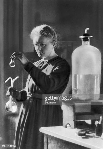 Marie Curie holds a test tube in her laboratory
