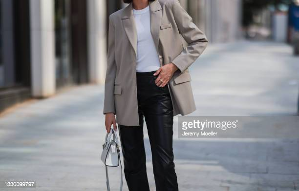 Marie Danker wearing white H&M top, black House of Dagmar leather pants, white Agneel leather bag and beige Aeryne blazer on July 16, 2021 in...